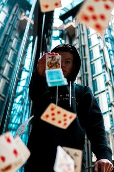 boy holding up playing cards