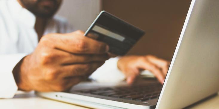 man entering credit card information on laptop